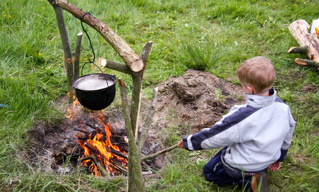boy cooking on camp fire